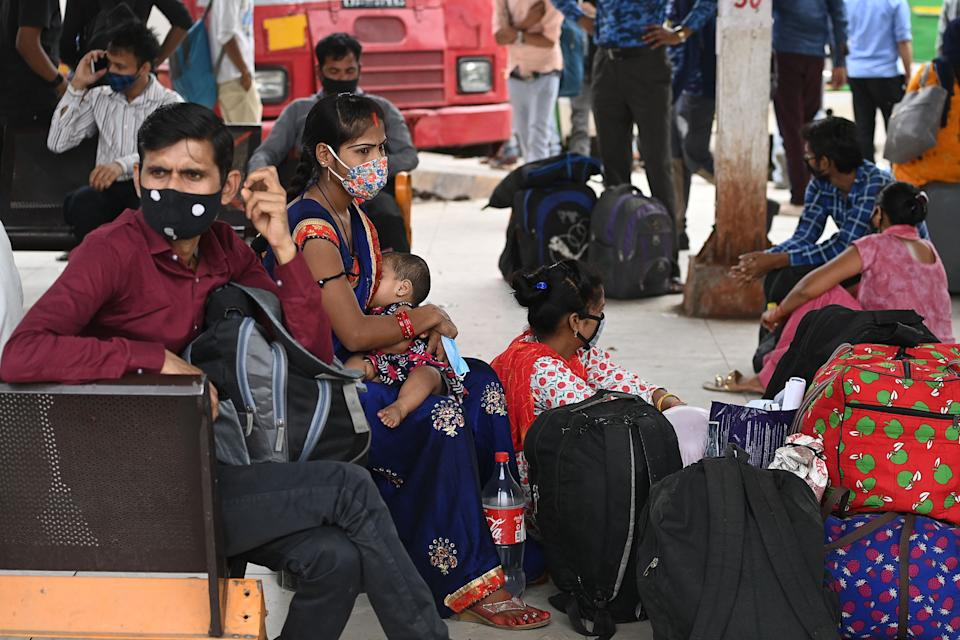 People wait to get on a bus at a station in New Delhi on April 20, 2021, to leave for their native places as India battles a record-breaking spike in Covid-19 coronavirus infections that has forced the capital into a week-long lockdown. (Photo by Sajjad HUSSAIN / AFP) (Photo by SAJJAD HUSSAIN/AFP via Getty Images)