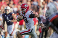 Georgia quarterback Stetson Bennett (13) carries the ball for a first down against Auburn during the second half of an NCAA college football game Saturday, Oct. 9, 2021, in Auburn, Ala. (AP Photo/Butch Dill)