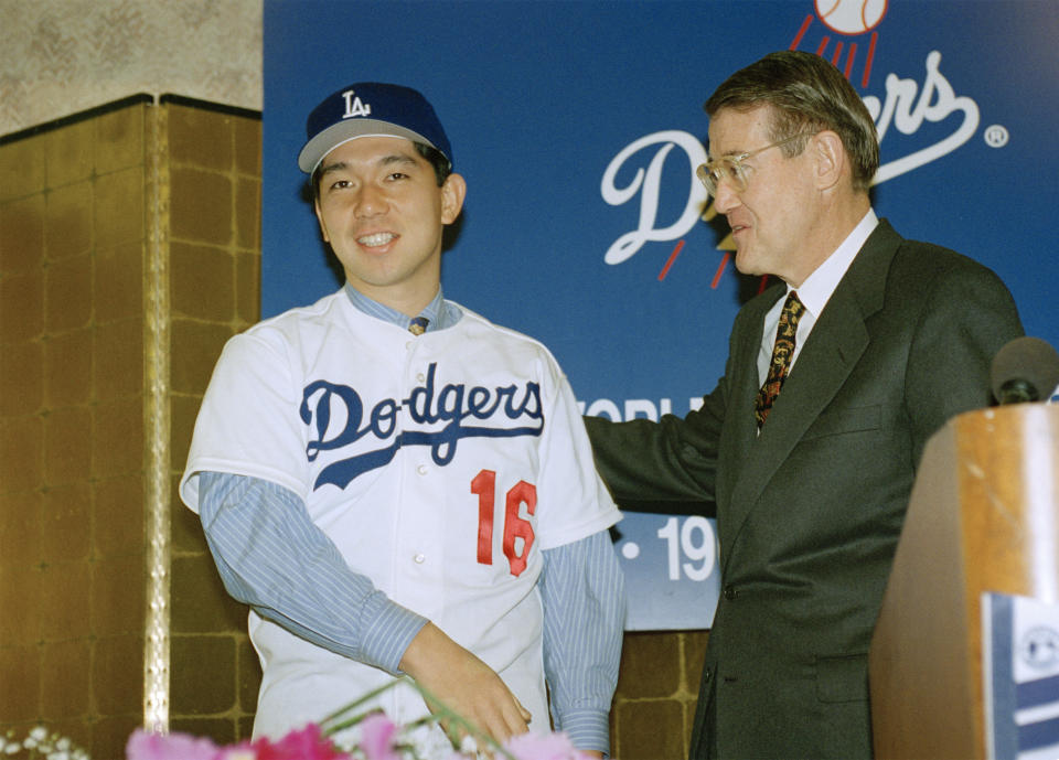 Hideo Nomo, left, an all-star pitcher in Japan, smiles with Los Angeles Dodgers president Peter O'Malley during a news conference in Los Angeles, Feb. 13, 1995, to announce the signing of Nomo to a minor league contract with the team. Nomo will have a chance to make the major league team this year if the baseball strike ends. (AP Photo/Nick Ut)