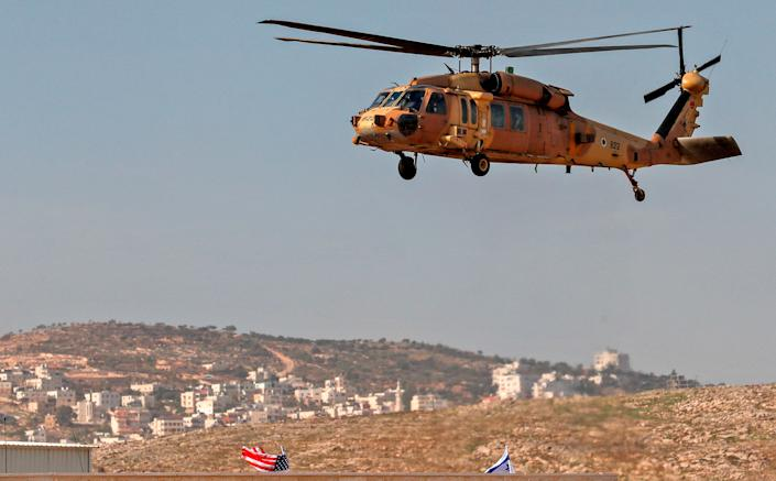 """An Israeli airforce helicopter carrying US Secretary of State Mike Pompeo hovers over the settlers industrial park of Sha'ar Binyamin, with the Palestinian village of Burqa in the background, in the occupied West Bank on Nov. 19<span class=""""copyright"""">Ahmad Gharabli—AFP/Getty Images</span>"""