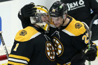 Boston Bruins goaltender Jeremy Swayman (1) and defenseman Brandon Carlo (25) celebrate their victory over the New York Rangers after an NHL hockey game, Thursday, May 6, 2021, in Boston. (AP Photo/Elise Amendola)