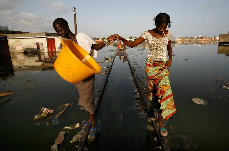 FILE - In this Sept. 10, 2008 file photo girls hold hands to keep their balance as they walk the rails of flooded train tracks in Thiaroye Sur Mer, on the outskirts of Dakar, Senegal Wednesday, Sept. 10, 2008. U.N. climate experts say global warming accelerated since the 1970s, breaking more countries' temperature records than ever before. The World Meteorological Organization's analysis Wednesday, July 3, 2013 calls the first decade of the new millennium an unprecedented era of climate extremes ranging from heat waves in Europe and Russia, to droughts in the Amazon Basin, Australia and East Africa, to huge storms like Tropical Cyclone Nargis and Hurricane Katrina.(AP Photo/Rebecca Blackwell, File)