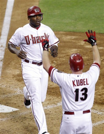 Arizona Diamondbacks' Justin Upton and Jason Kubel (13) score on a base hit by Miguel Montero against the Colorado Rockies during the seventh inning of a baseball game, Tuesday, July 24, 2012, in Phoenix. (AP Photo/Matt York)