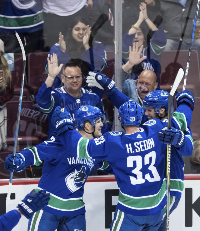 Vancouver Canucks' Daniel Sedin, Henrik Sedin and Alexander Edler, from left, all of Sweden, celebrate Daniel Sedin's goal against the Arizona Coyotes during the second period of an NHL hockey game Thursday, April 5, 2018, in Vancouver, British Columbia. (Darryl Dyck//The Canadian Press via AP)