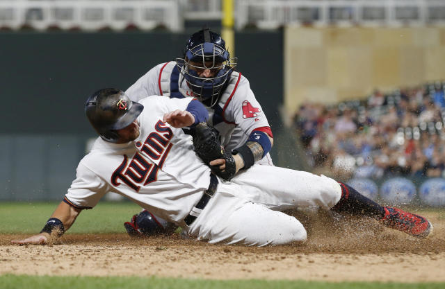 Boston Red Sox catcher Sandy Leon tags out Minnesota Twins' Robbie Grossman, who tried to score from third on a fly-out by Ehire Adrianza during the eighth inning of a baseball game Tuesday, June 19, 2018, in Minneapolis Grossman had two RBIs in the Twins' 6-2 win. (AP Photo/Jim Mone)