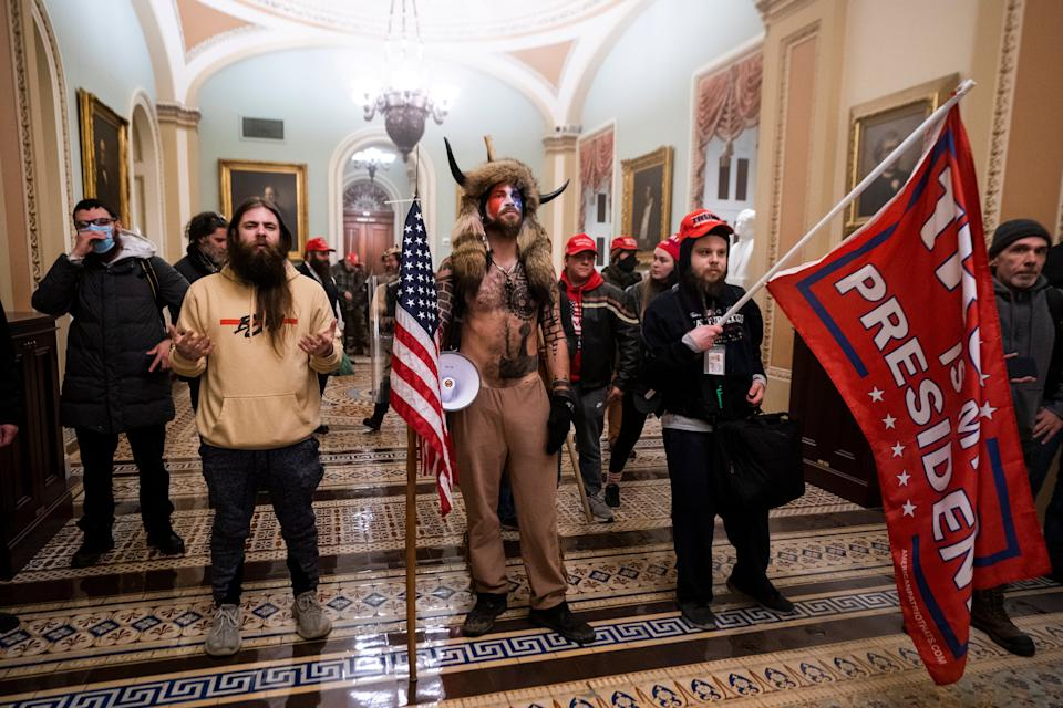 Jake Angeli, center, stands in the US Capitol dressed in fur and horns after Trump supporters stormed the building on 6 January in an effort to force legislators to overturn the election results.   (EPA)