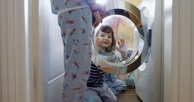 Young woman putting laundry in a washing machine while her kids help her (Photo: Thanasis Zovoilis via Getty Images)
