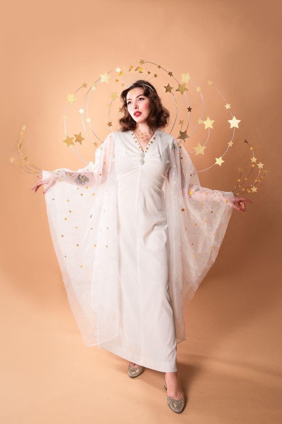 """<p>Inspired by the classic 1940s film <em>Ziegfeld Girl,</em> this costume is sheer glamour—and easy to make with a simple white maxi dress you can quickly alter.</p><p><strong>Get the tutorial at <a href=""""http://keikolynn.com/2018/10/ziegfeld-girl-costume-hedy-lamarr/"""" rel=""""nofollow noopener"""" target=""""_blank"""" data-ylk=""""slk:Keiko Lynn"""" class=""""link rapid-noclick-resp"""">Keiko Lynn</a>.</strong></p><p><a class=""""link rapid-noclick-resp"""" href=""""https://www.amazon.com/Cutouts-Shining-Glitter-Cardboard-Metallic/dp/B07V8G7PR4?tag=syn-yahoo-20&ascsubtag=%5Bartid%7C10050.g.4571%5Bsrc%7Cyahoo-us"""" rel=""""nofollow noopener"""" target=""""_blank"""" data-ylk=""""slk:SHOP GOLD STAR CUTOUTS"""">SHOP GOLD STAR CUTOUTS</a><strong><br></strong></p>"""
