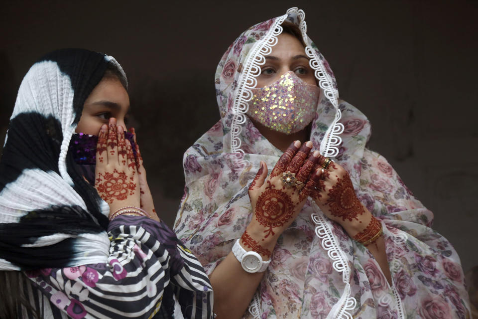 Muslim women with their hands painted with traditional henna pray during an Eid al-Fitr prayer at historical Badshahi mosque, in Lahore, Pakistan, Thursday, May 13, 2021. Millions of Muslims across the world are marking a muted and gloomy holiday of Eid al-Fitr, the end of the fasting month of Ramadan, a usually joyous three-day celebration that has been significantly toned down as coronavirus cases soar. (AP Photo/K.M. Chaudary)