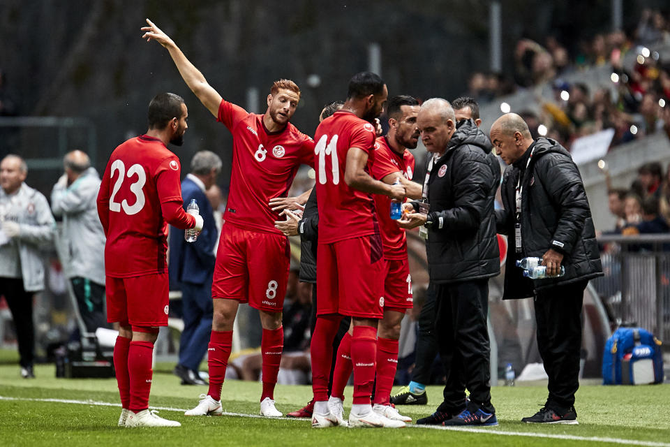 Tunisia players go to the sideline for mid-game nourishment during an injury delay against Portugal. (Getty)
