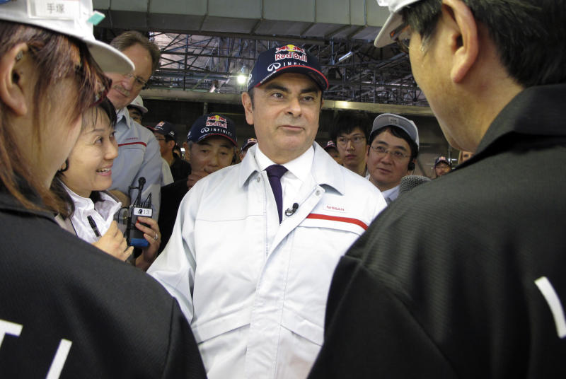 "Nissan Motor Co. President Carlos Ghosn, center, talks with plant workers as he tours the automaker's Tochigi Infiniti plant in Kaminokawa machi, Tochigi prefecture, north of Tokyo, Tuesday, May 14, 2013.  Nissan Motor Co. President Ghosn welcomed the yen's recent decline to what he called ""neutral"" levels for the Japanese automaker's profitability, but said Tuesday it must drop further to be ""normal."" (AP Photo/Yuri Kageyama)"