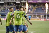 Seattle Sounders forward Fredy Montero, right, is hugged by Alex Roldan (16) after Montero scored against Minnesota United during the second half of an MLS soccer match Friday, April 16, 2021, in Seattle. The Sounders won 4-0. (AP Photo/Ted S. Warren)