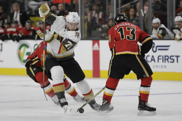 Vegas Golden Knights center William Karlsson (71) vies for the puck against Calgary Flames left wing Johnny Gaudreau (13) during the second period of an NHL hockey game Friday, Nov. 23, 2018 in Las Vegas. (AP Photo/Joe Buglewicz)