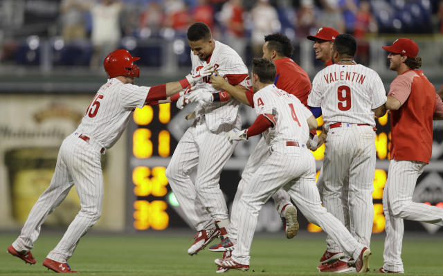 Philadelphia Phillies' Aaron Altherr, second from left, celebrates with teammates after hitting a game-winning two-run double off St. Louis Cardinals relief pitcher Matt Bowman during the 10th inning of a baseball game, Monday, June 18, 2018, in Philadelphia. Philadelphia won 6-5. (AP Photo/Matt Slocum)