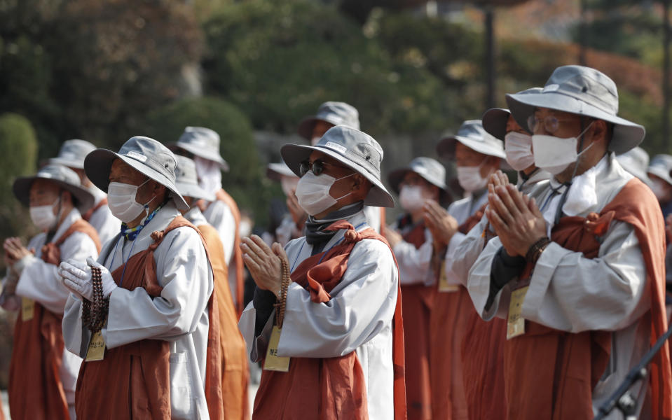 Buddhist monks pray upon their arrival at Bongeun temple in Seoul, South Korea, Tuesday, Oct. 27, 2020. About 100 monks and believers marched the 500-kilometer (310-mile) pilgrimage to wish for the country to overcome the coronavirus. (AP Photo/Lee Jin-man)