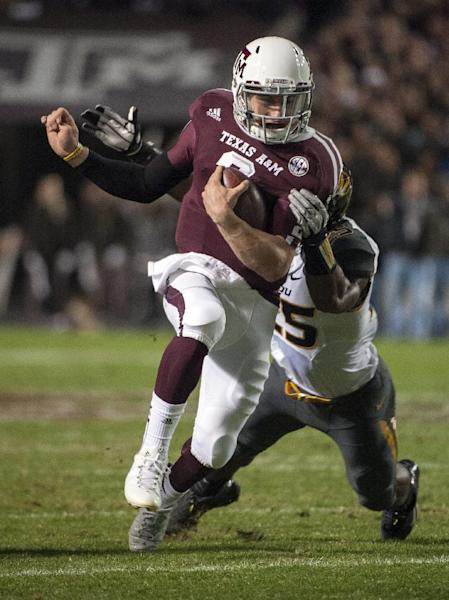 Texas A&M's Johnny Manziel, front, runs through Missouri's Zaviar Gooden (25) during the first quarter of an NCAA college football game on Saturday, Nov. 24, 2012, in College Station, Texas. (AP Photo/Dave Einsel)
