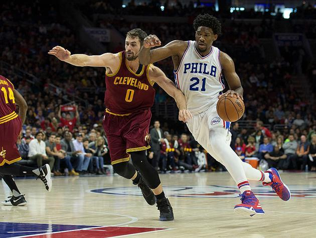 Joel Embiid moves past Kevin Love. (Getty Images)