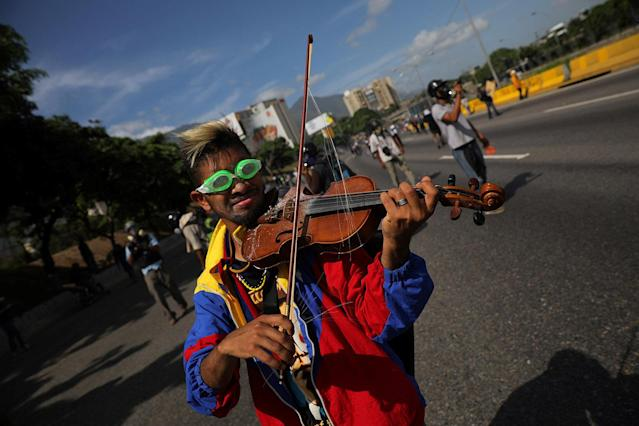 <p>An opposition supporter plays the violin during a rally against President Nicolas Maduro in Caracas, Venezuela, May 18, 2017. (Photo: Carlos Barria/Reuters) </p>