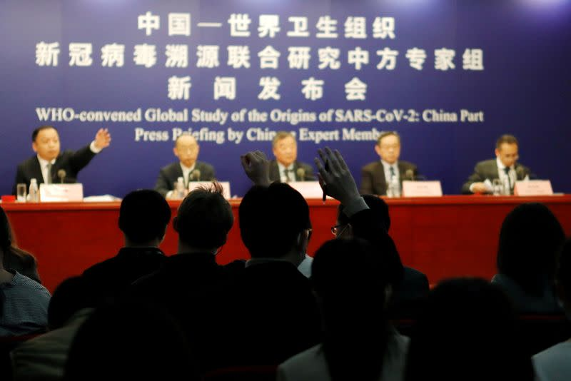 Journalists raise hands at a news conference on the WHO-China joint study, in Beijing