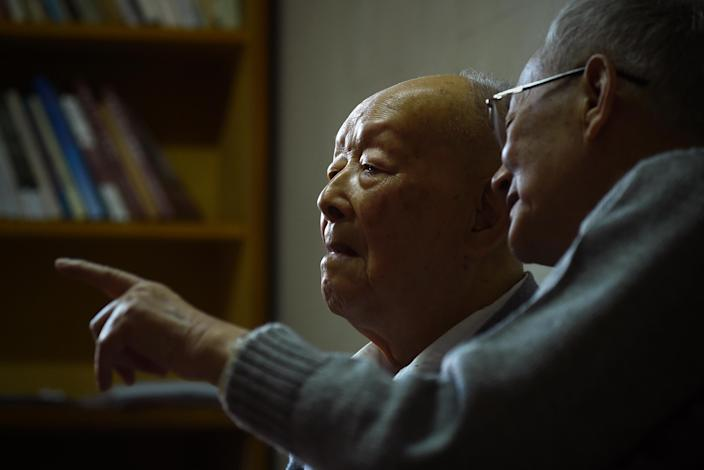 "Zhou Youguang (L), commonly known as the ""father of Pinyin"", talks to his son Zhou Xiaoping at his home in Beijing on January 11, 2015 (AFP Photo/Wang Zhao)"