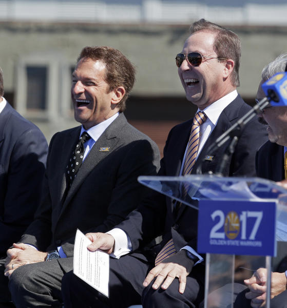 Golden State Warriors owners Peter Guber, left, and Joe Lacob, right, laugh during an announcement, in San Francisco, Tuesday, May 22, 2012, that the NBA basketball team wants to return to San Francisco. The Warriors unveiled plans to build an arena at Piers 30-32. The waterfront site near the San Francisco-Oakland Bay Bridge is just blocks from the San Francisco Giants' ballpark and the downtown financial district. (AP Photo/Eric Risberg)
