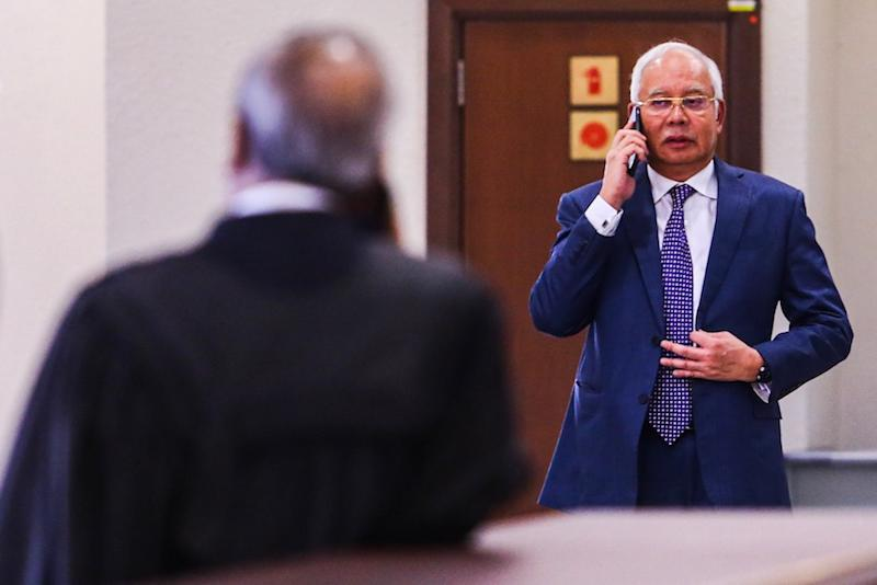 Datuk Seri Najib Razak makes a call during recess for his SRC International trial at the Kuala Lumpur Courts Complex August 19, 2019. — Picture by Hari Anggara