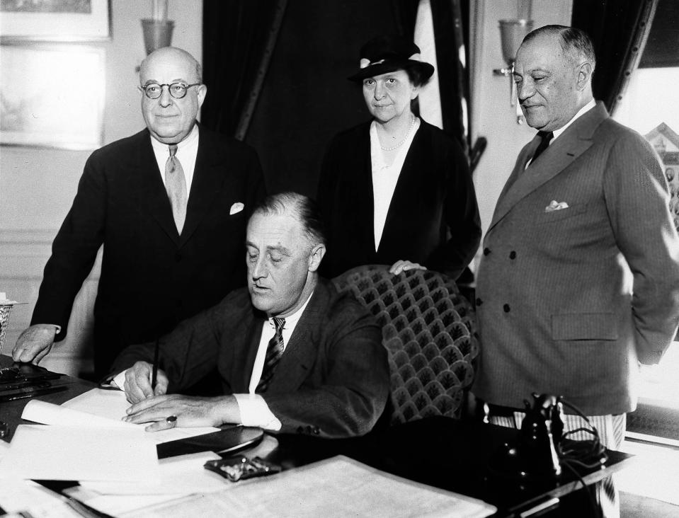 FILE - In this June 6, 1933 file photo, President Franklin D. Roosevelt is shown signing the Wagner Unemployment Bill at the White House in Washington. Standing, from left are: Rep. Theodore A. Peyser, D-N.Y.; Labor Secretary of Labor Frances Perkins; and Sen. Robert Wagner, D-N.Y. (AP Photo, File)