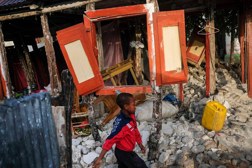 A boy walks past his home destroyed by the 7.2 magnitude earthquake, in Maniche, Haiti on Aug. 24, 2021.
