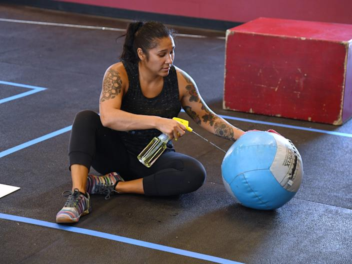 Michelle Crothers sprays disinfectant on a medicine ball after working out at CrossFit Apollo, which opened for the first time since closing on March 17 because of the coronavirus (COVID-19) pandemic on May 29, 2020 in Las Vegas, Nevada