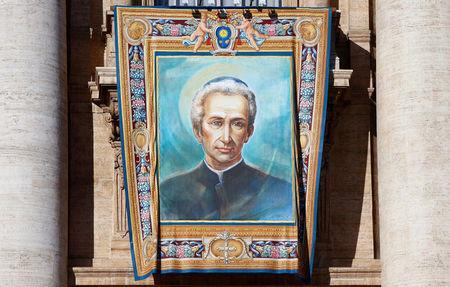 The tapestry of Lodovico Pavoni, one of the seven new saints, hangs from Saint Peter's Basilica before the start of a canonization mass led by Pope Francis at the Vatican October 16, 2016. REUTERS/Tony Gentile