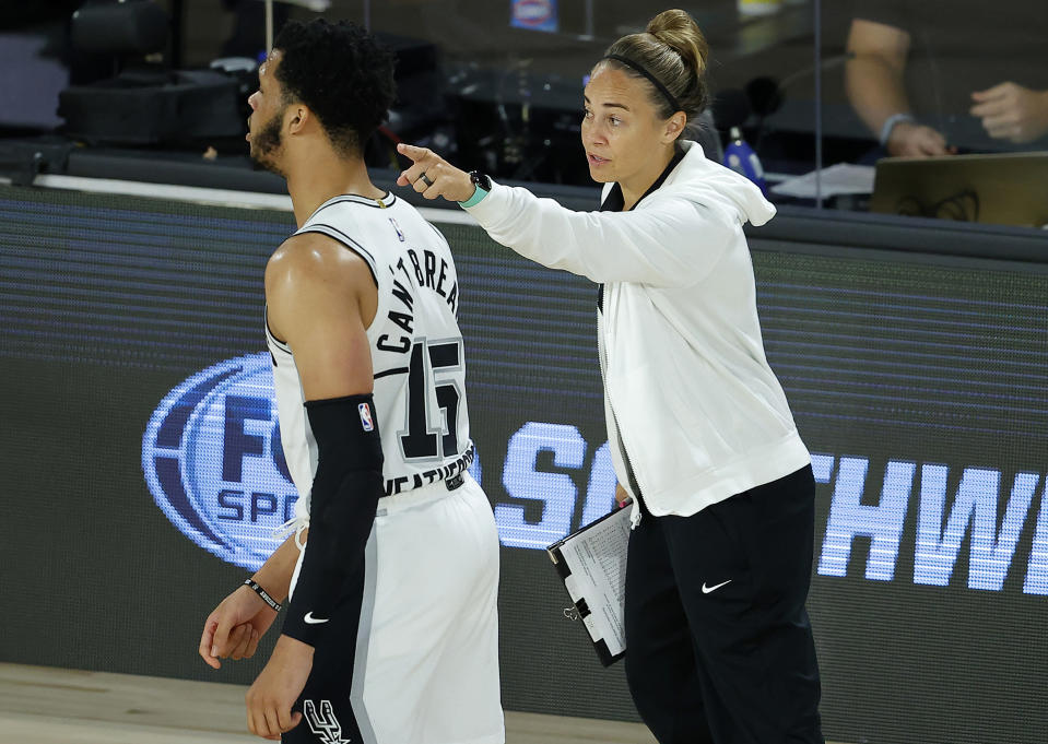 FILE - San Antonio Spurs assistant coach Becky Hammon talks with Quinndary Weatherspoon (15) during the second half of an NBA basketball game against the Utah Jazz in Lake Buena Vista, Fla., in this Friday, Aug. 7, 2020, file photo. Becky Hammon became the first woman to direct a team in NBA history, taking over the San Antonio Spurs on Wednesday night, Dec. 30, 2020, against the Los Angeles Lakers following Gregg Popovich's ejection in the first half.(Kevin C. Cox/Pool Photo via AP, File)