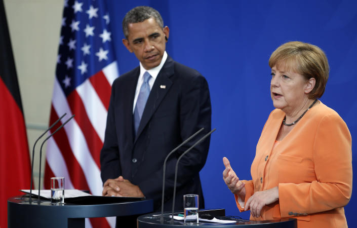 FILE - In this June 19, 2013, file photo U.S. President Barack Obama listens to German Chancellor Angela Merkel, right, address media at a joint press conference at the chancellery in Berlin. Merkel, publicly questioned the legitimacy of U.S. NSA surveillance programs, while standing next to Obama during his Berlin visit. Though his approval ratings in Europe have long been high, those numbers have slipped in his second term. And so has European approval for his administration's international policies. A Pew Research Center poll conducted this spring, before the NSA programs were revealed, showed that support for his foreign policies was down in most of the countries surveyed, including a 14 point drop in Britain and a 12 point drop in France. (AP Photo/Michael Sohn, File)