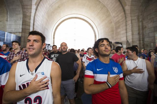 U.S. soccer fans stand for the Star Spangled Banner at the start of the team's 2014 World Cup Group G soccer match against Germany at a viewing party under the Manhattan Bridge in New York June 26, 2014. REUTERS/Lucas Jackson (UNITED STATES - Tags: SPORT SOCCER WORLD CUP)