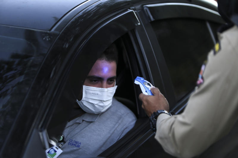 NITEROI, BRAZIL - MAY 11: A member of the Municipal Civil Guard checks the temperature of a driver at a blockade on the border between the municipalities of Niteroi during the first lockdown day in the coronavirus (COVID-19) pandemic on May 11, 2020 in Niteroi, Brazil. The guards checks the temperature at people during a operation. According to the Brazilian Health Ministry, Brazil has 163,000 positive cases of coronavirus (COVID-19) and a total of 11,123 deaths. (Photo by Luis Alvarenga/Getty Images)