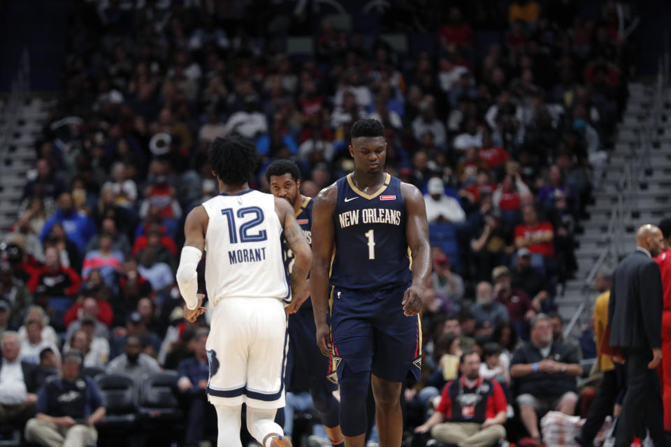 New Orleans Pelicans forward Zion Williamson (1) walks past Memphis Grizzlies guard Ja Morant (12)