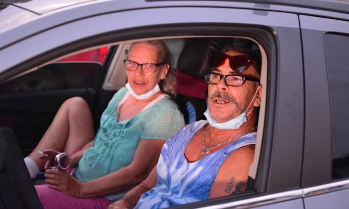 Leann Carlsen and James Virgil, local residents, wait for the movie to start in their cars at the Ocala drive-in theatre.