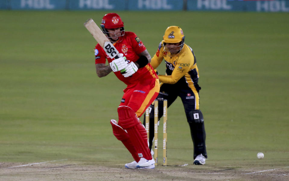 Islamabad United' Alex Hales, front, plays a shot while Peshawar Zalmi' Kamran Akmal watches during a Pakistan Super League T20 cricket match between Islamabad United and Peshawar Zalmi at the National Stadium, in Karachi, Pakistan, Saturday, Feb. 27, 2021. (AP Photo/Fareed Khan)