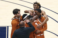 Texas players celebrate after defeating West Virginia in an NCAA college basketball game Saturday, Jan. 9, 2021, in Morgantown, W.Va. (AP Photo/Kathleen Batten)