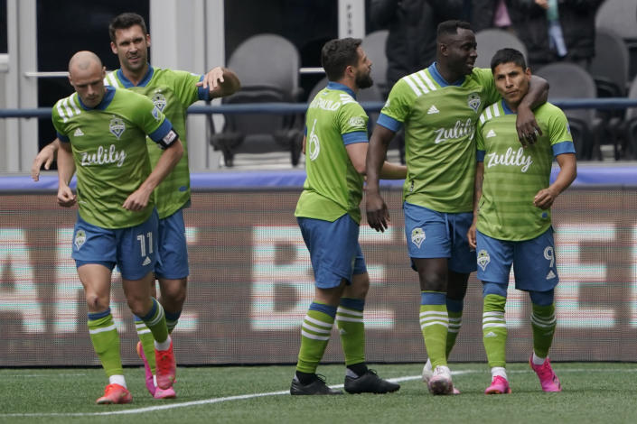 Seattle Sounders forward Raul Ruidiaz, right, is greeted by teammates after he scored a goal against Atlanta United during the first half of an MLS soccer match, Sunday, May 23, 2021, in Seattle. (AP Photo/Ted S. Warren)