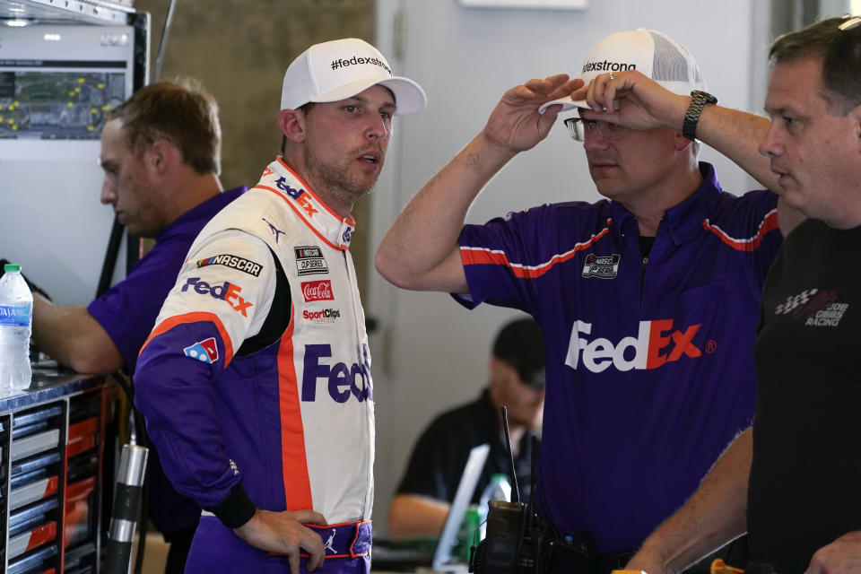Denny Hamlin talks with a crew member during practice for the NASCAR Cup Series auto race at Indianapolis Motor Speedway, Saturday, Aug. 14, 2021, in Indianapolis. (AP Photo/Darron Cummings)