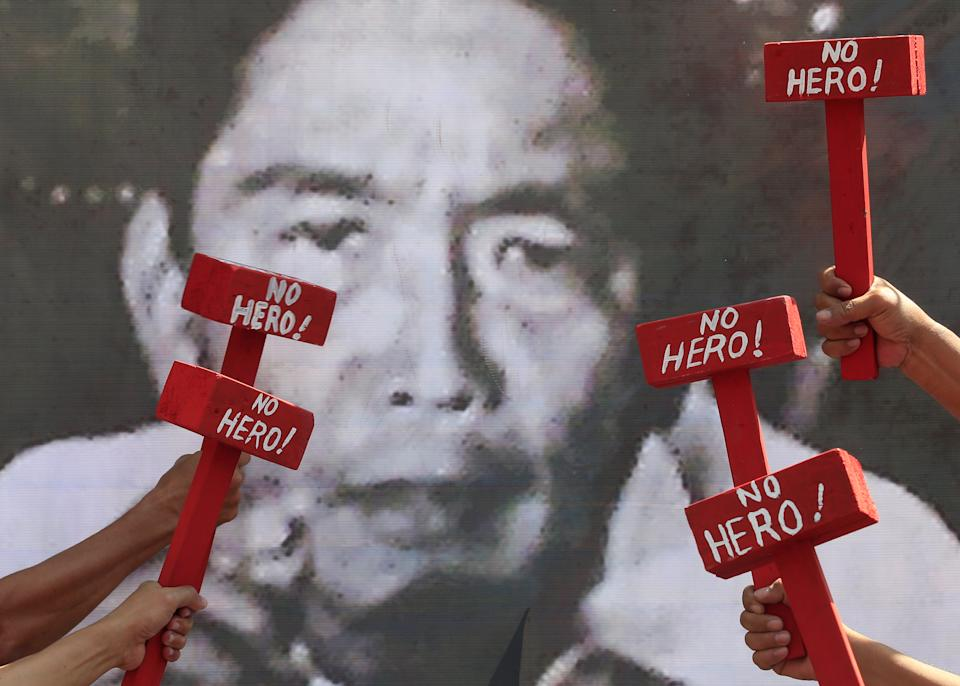 FILE PHOTO: Protestors hold mock hammers with words 'No Hero' in front of a portrait of the late dictator Ferdinand Marcos as they denounce his burial at the Libingan ng mga Bayani (Heroes' cemetery) during a protest outside the presidential palace in metro Manila, Philippines November 22, 2016. (Source: REUTERS/Romeo Ranoco)