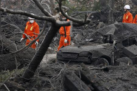 Rescuers walk past a wrecked car on a damaged road covered with debris a day after an explosion at a Sinopec Corp oil pipeline in Huangdao