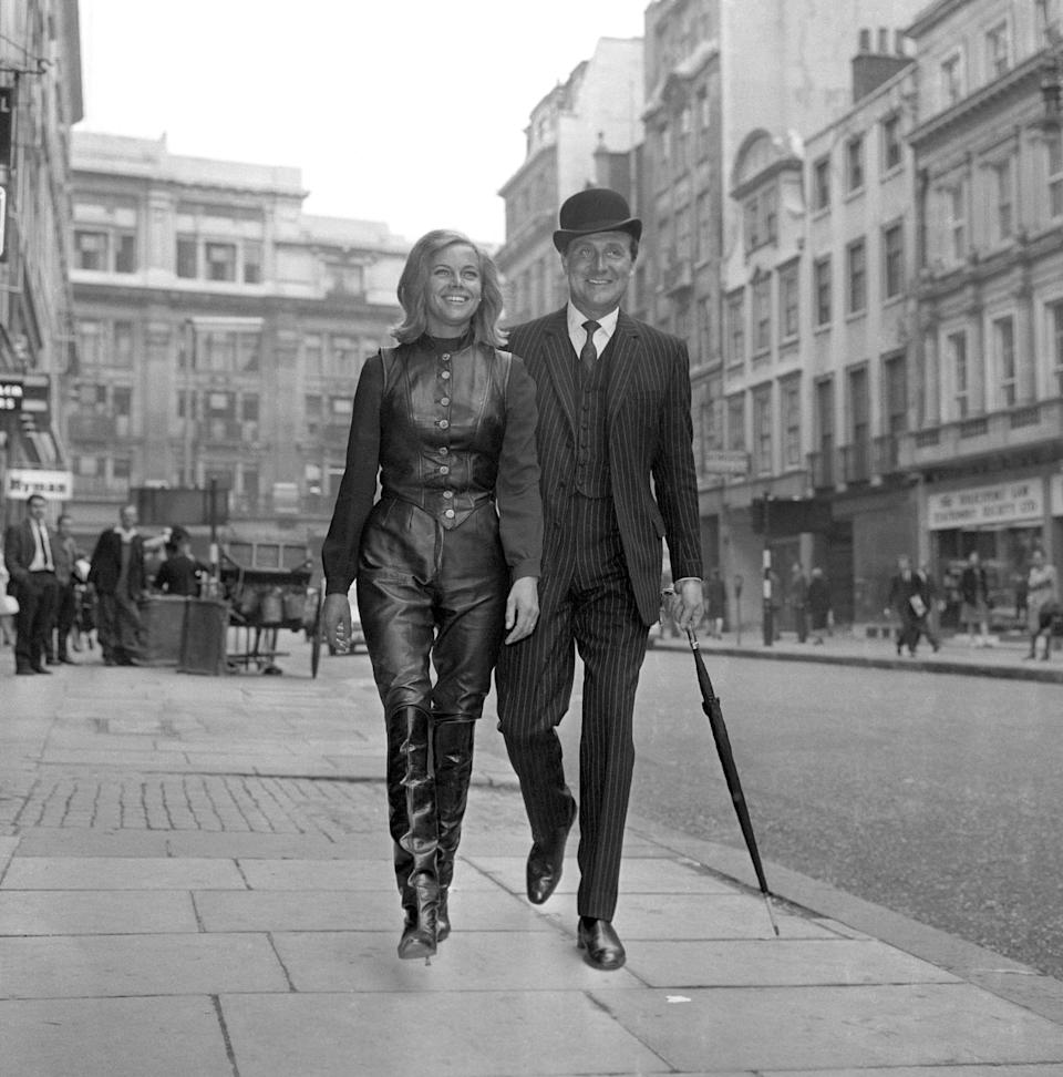 """HONOR BLACKMAN (CATHERINE GALE), OF THE ATV THRILLER SERIES """"THE AVENGERS"""" TYPIFIES THE PIN UP GIRL OF CONTEMPARY BRITAIN. SHE IS THE SYMBOL OF THE JET AGE WOMAN, WITH LEATHER JERKIN, BREECH & HIGH BOOTS. HERE WITH PATRICK MaCNEE AS THEY ARRIVE AT SELBYS RESTAURANT.   (Photo by PA Images via Getty Images)"""