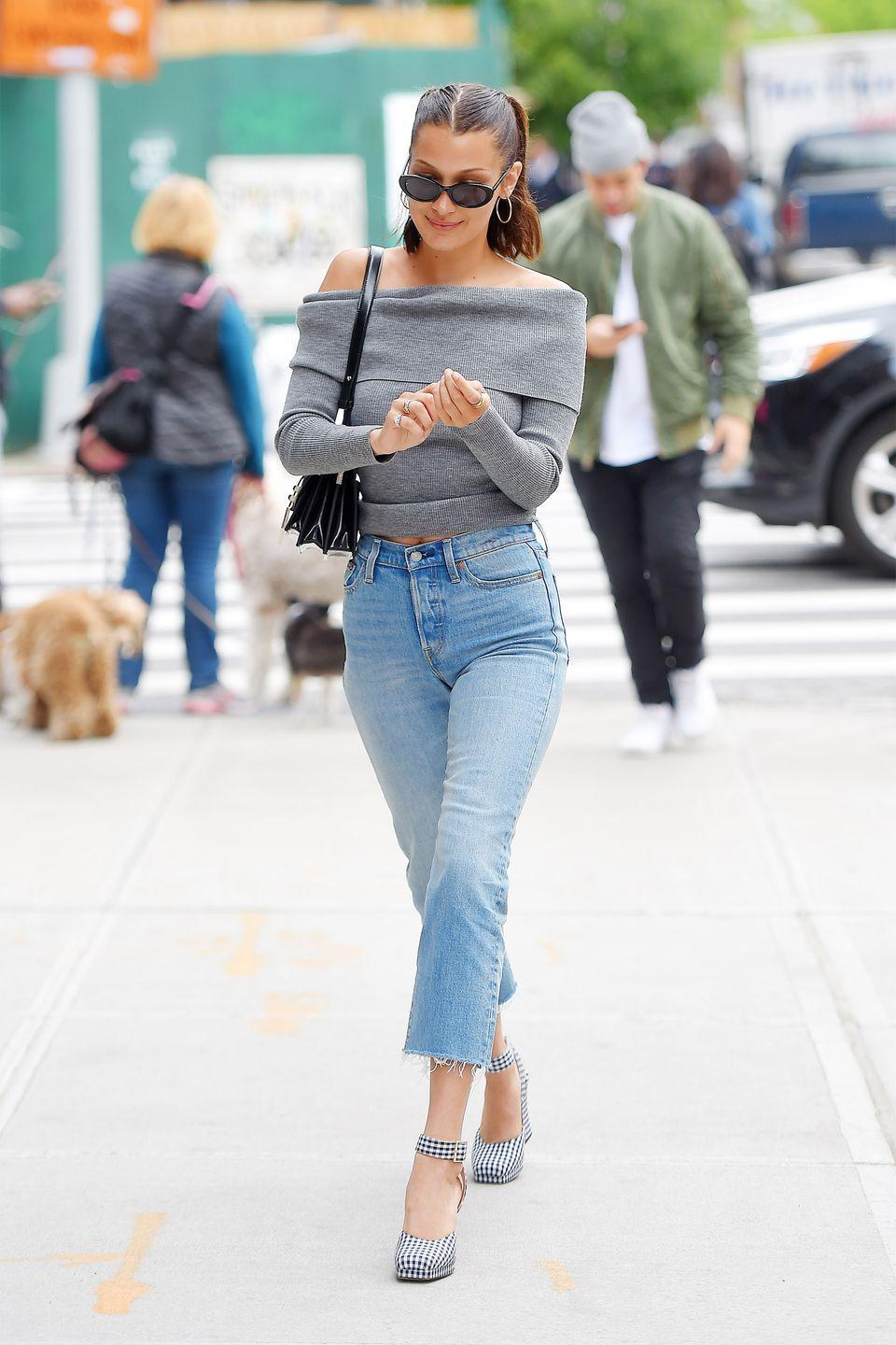 <p>In an Aritzia off-the-shoulder sweater, Levi's straight-leg jeans, gingham platform heels, Roberi & Fraud sunglasses, hoop earrings and a black leather shoulder bag while out in NYC.</p>