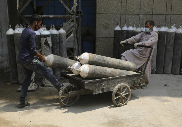 Workers load oxygen cylinders onto a hand cart to be carried inside the COVID-19 wards at a government run hospital in Jammu, India, Friday, May 7, 2021. With coronavirus cases surging to record levels, Indian Prime Minister Narendra Modi is facing growing pressure to impose a harsh nationwide lockdown amid a debate whether restrictions imposed by individual states are enough. (AP Photo/Channi Anand)