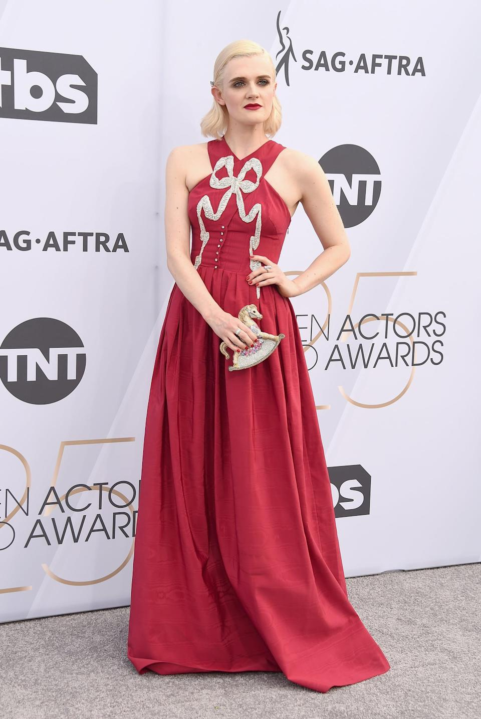 <p>Wearing a red Sandra Mansour gown, Giuseppe Zanotti shoes, a Judith Leiber clutch, Neil Lane jewelry, and a Swarovski hair accessory.</p>