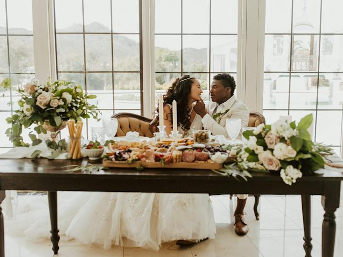 A groom brushes a bride's lip with his thumb as they sit on a couch behind an ornate table.