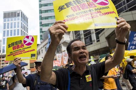Pro-democracy protesters shout during a march to demand lawmakers reject a Beijing-vetted electoral reform package for the city's first direct chief executive election in Hong Kong, China June 14, 2015. REUTERS/Tyrone Siu