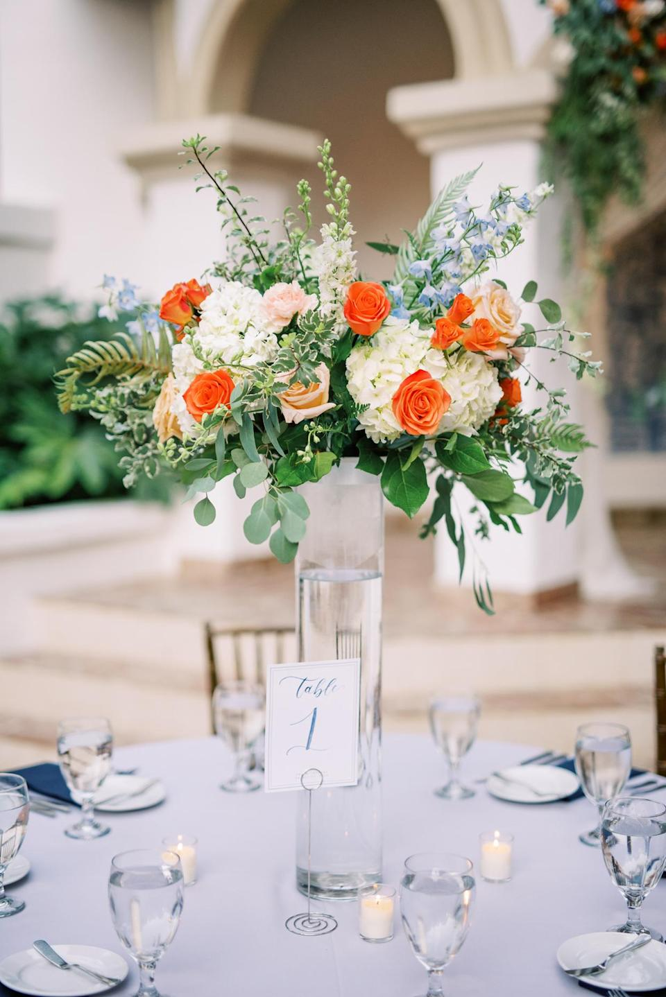 """<p>The centerpieces, a mix of tall and low arrangements, were whimsical and romantic, much like the property, notes the bride: """"It was important to highlight the venue, so the pops of color played well off the surrounding gardens and Spanish details.""""</p>"""