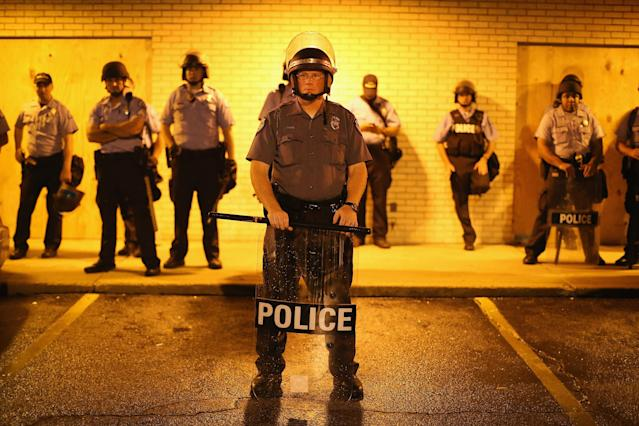 <p>Police stand guard before the mandatory midnight curfew on August 16, 2014 in Ferguson, Missouri. The curfew was imposed on Saturday in an attempt to reign in the violence that has erupted nearly every night in the suburban St. Louis town since the shooting death of teenager Michael Brown by a Ferguson police officer on August 9. (Scott Olson/Getty Images) </p>